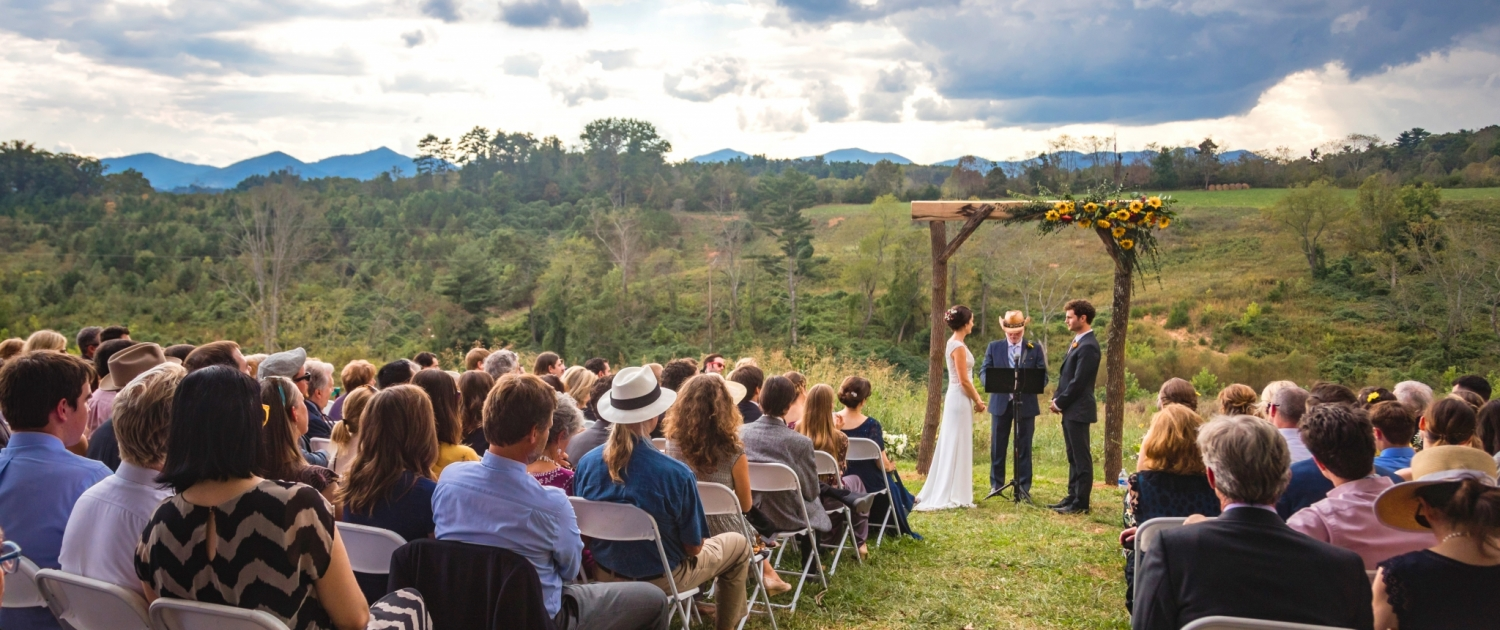 Wedding ceremony and guests with farm and mountain view