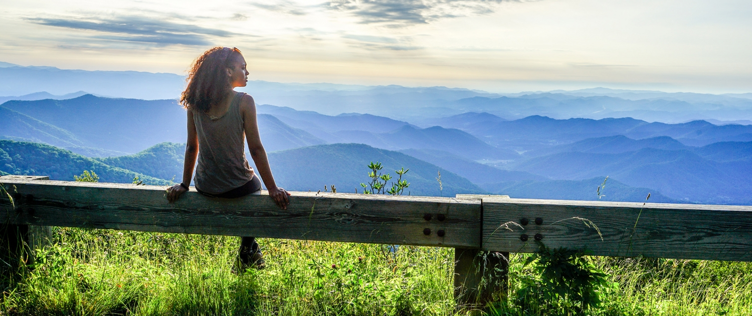 woman sitting near Blue Ridge Parkway looking out over Southern Appalachian mountains
