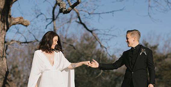 wedding couple holding hands near tree