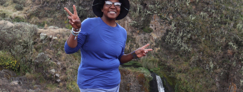 Allison standing in front of a waterfall on a hike in Olmoti Crater in Tanzania. Allison is wearing a blue shirt, blue skirt, black leggings, and hiking boots.