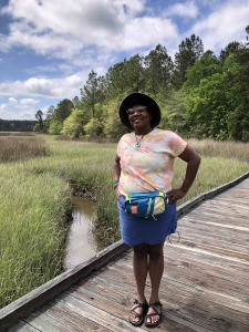 Allison is standing on a bridge over a small creek. She is wearing an orange, pink, and white tie die shirt, a blue skirt, and a teal fanny pack.