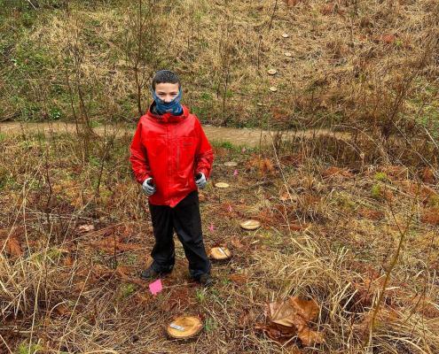 Youth volunteer with salamander plots in stream restoration area